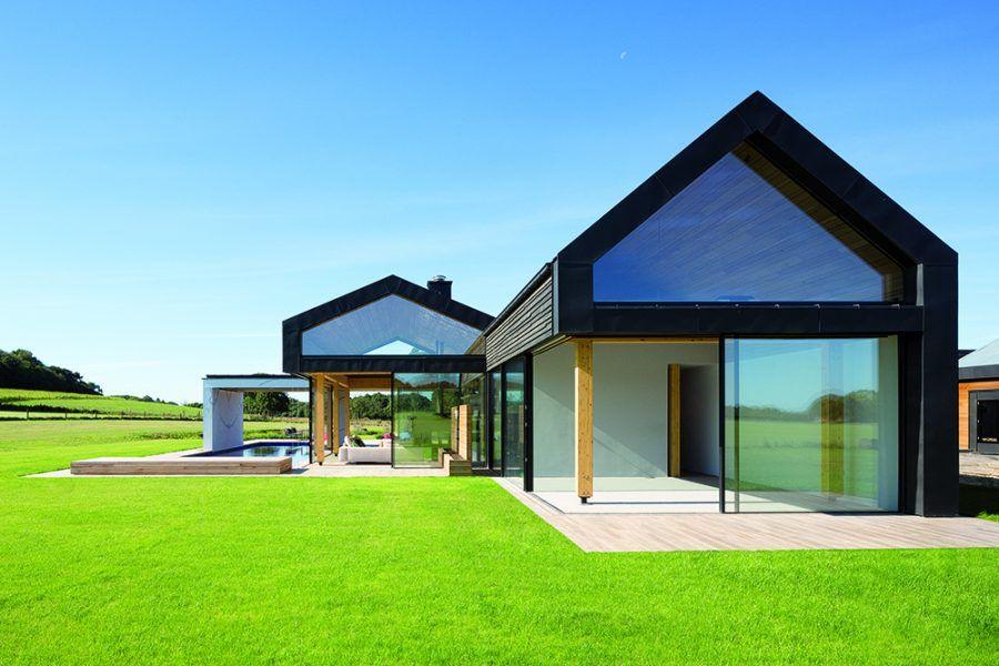 Pohľad z východu. V juhovýchodnej časti členitej farmy je veľká hlavná spálňa, na ktorú nadväzujú obývačka a terasa s bazénom. Vďaka impozantným skleneným plochám zasadeným do čiernych oceľových rámov a prísnej geometrii pôsobia objekty moderne, vďaka archetypálnemu tvaru sa zároveň harmonicky začlenili medzi pôvodné vidiecke stavby.