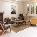 """Obývačka v retro štýle. Vystačí si s gaučom, dvoma rôznymi kreslami a """"vychodeným"""" kobercom. To všetko dopĺňa starožitný odkladací stolík v rohu a dve stojacie originálne svietidlá."""