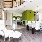 Obývačka prepojená s jedálňou a kuchyňou je veľká a vzdušná. Vizuálne sú oddelené odlišnou podlahou. Centrom denného priestoru je kozub, okolo ktorého sa vinie schodisko na horné poschodie do pokojnej časti so spálňami. Štýl, ktorý majiteľka zvolila, podčiarkuje aj tehlová stena v zemitých odtieňoch hnedej a béžovej farby.