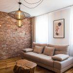 """Zvláštna požiadavka? Tmavšia tehlová stena na konci obývačky zmiernila dojem dlhého """"slíža"""". Od remeselníkov vyžadoval dizajnér obkladanie s primeranými nepravidelnosťami, aby tehly vyzerali prirodzene – ani tradičné murivo predsa nebývalo dokonale rovné."""