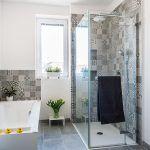 Šikovné riešenie. Kúpeľňa s oknom patrila k prednostiam pôvodného bytu. Zmestila sa sem vaňa aj sprchovací kút s vaničkou v úrovni podlahy. Vetracie potrubie skryli za predsadenú stenu s nikami, ktoré majú v sprchovacom kúte praktické využitie.