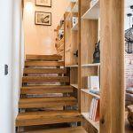 """Sila svetla. Vďaka drevenej policovej stene preniká svetlo do priestoru schodiska, čím sa zmiernil efekt """"komína"""". Oceľové nosné stĺpy tu museli ostať, sú však šikovne skryté za dreveným obkladom."""