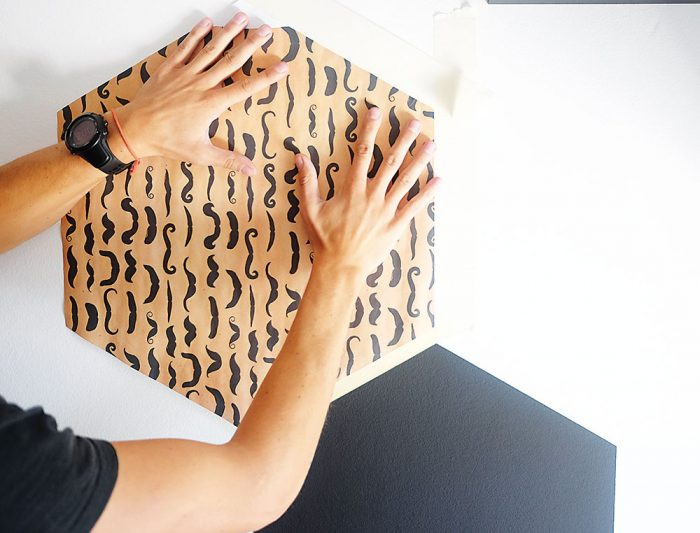 Šablónu priložíme na stenu. Okolo nej nalepíme ochrannú pásku, ktorá nám zabezpečí, že pri natieraní nezašpiníme nič naokolo.