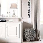 Chodba, kuchyňa a jedáleň sú zariadené svetlým nábytkom a tlmenými farbami, tvoria kontrast k tmavej obývačke.