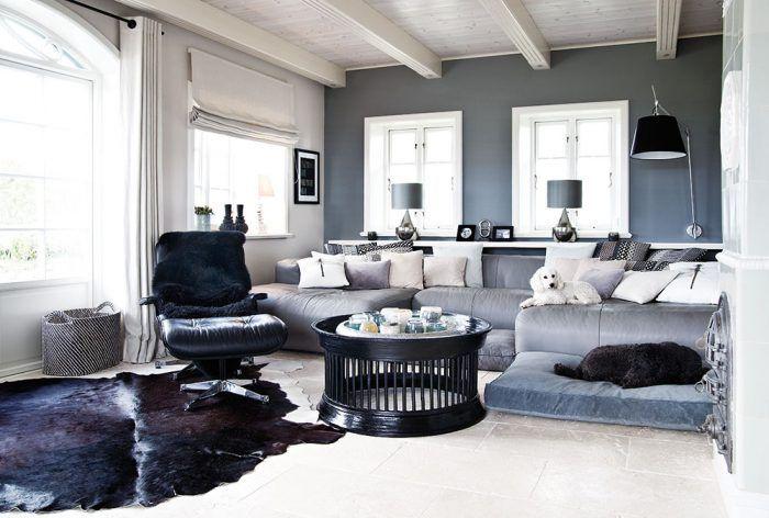 Sivá farba na stenách a sedačke dominuje obývačke. Napriek tomu miestnosť nepôsobí tmavo ani pochmúrne, keďže dostatok svetla dnu privádzajú biele drevené okná s kovovými kľučkami.