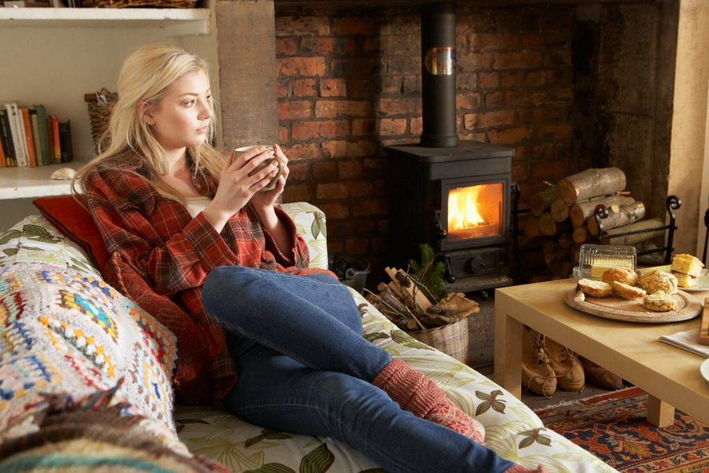Young woman relaxing by fire with hot drink