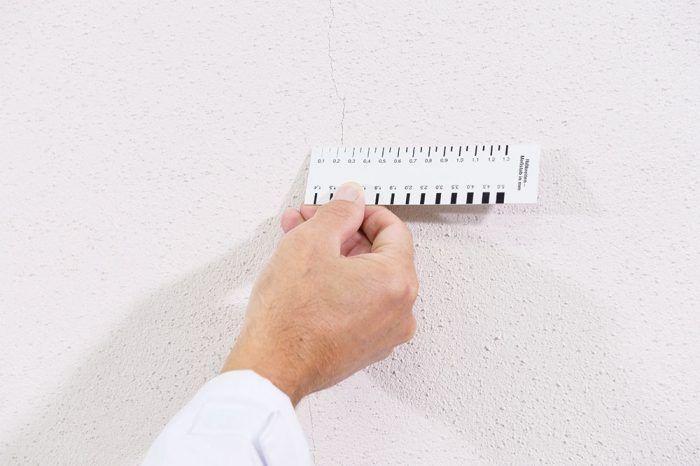 Pred aplikáciou náteru na opravu trhlín sa najskôr overí šírka trhlín pomocou kalibrovanej pomôcky.