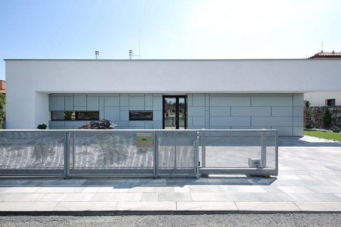 """V kontakte s ulicou využíva objekt celú šírku parcely – okoloidúci vníma jasne čitateľný rám domu, ktorý vytvára bielu horizontálnu líniu a vymedzuje vstupný priestor. Za týmto """"vstupným portálom"""" sa nachádza privátna zóna."""