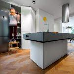 Kuchynský ostrov uprostred miestnosti poskytuje pracovné plochy aj miesto na barové stolovanie, vo vysokej vstavanej skrini je za nenápadnými bielymi dverami priestor na odkladanie, ale aj na chladničku, umývačku riadu a rúru.