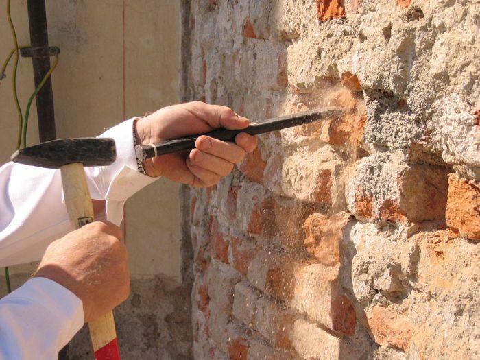 1. Odstránime všetky zvetrané, vlhkosťou a soľami poškodené omietky a maltu zo škár. Sutinu ihneď odvezieme a zabezpečíme vetranie steny.