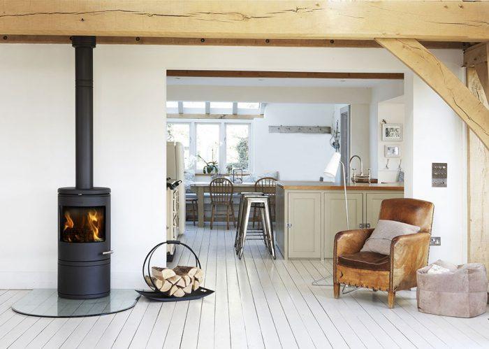 Kuchyňa v škandinávskom štýle lagom s kozubom a kreslom
