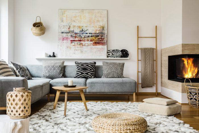 Obývačka v škandinávskom štýle lagom so šedou sedačkou a drevenými doplnkami