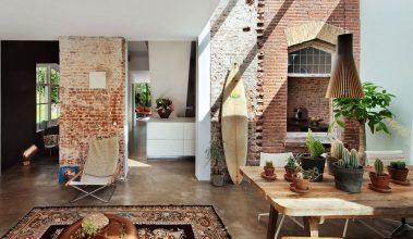 Obývačka v štýle lagom, tehlová stena, drevený stôl, opretý surf