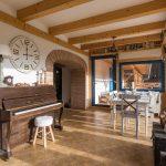 mlyn zrekonštruovaný na bývanie na samote pri Banskej Štiavnici,drevený interiér so stoličkami a stolom a klavírom