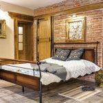 Spálňa v historickom dome s kovovou posteľou a tehlovou stenou