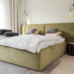 Čalúnená posteľ s poduškami v pastelových tónoch