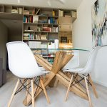 Jedálenský kút so skleným stolom a bielymi plastovými stoličkami