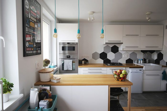 Moderná jednoduchá bieločierna kuchyňa v rodinnom dome s kuchynským ostrovčekom