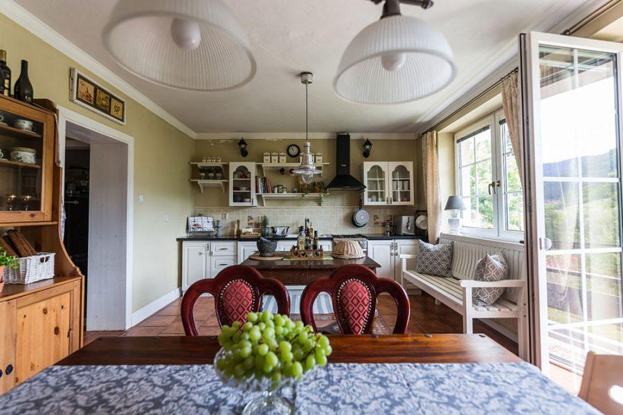 Obývačka spojená s kuchyňou v rustikálnom štýle s jedálenským stolom a stoličkami