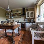 Vidiecka kuchyňa s masívnym dreveným stolom a bielou lavicou