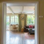 Pohľad cez dvere do rustikálnej obývačky