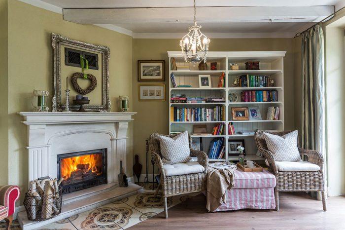 Obývačka s kozubom, prútenými kreslami a knižnicou