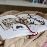 Otvorená kniha s okuliarmi na posteli