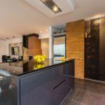 kuchynský ostrovček s lesklou ciernou pracovnou plochou a úložnými priestormi