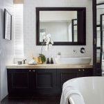 Monochromatická koncepcia a jednoduchosť dominujú aj v kúpeľni. Zelená papraď v kvetináči odkazuje na rastlinný vzor koberca v obývačke.
