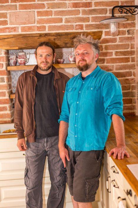 dvaja muži pri tehlovej stene