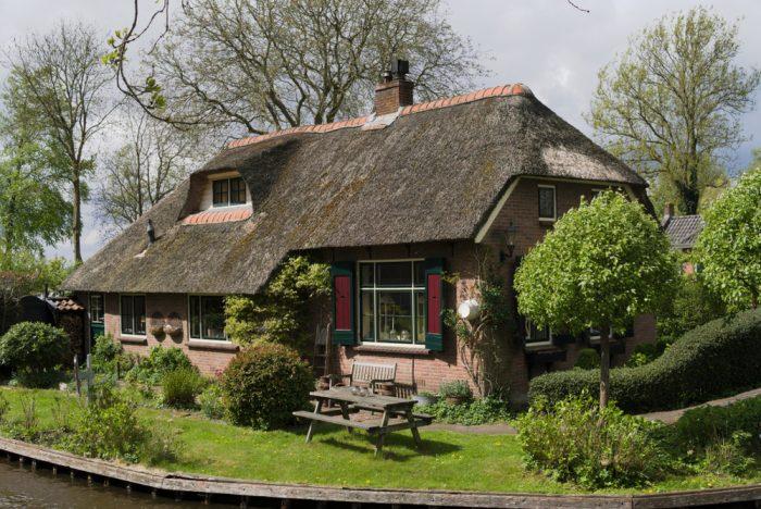 Tehlová chata so slamenou strechou v Holandsku.