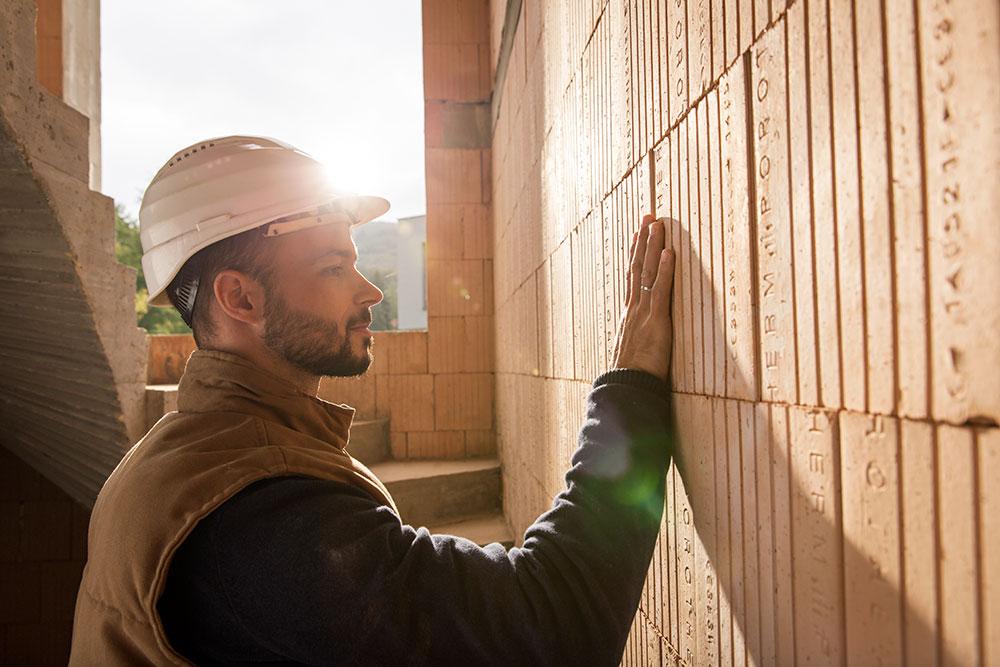muž sa dotýka tehlovej steny
