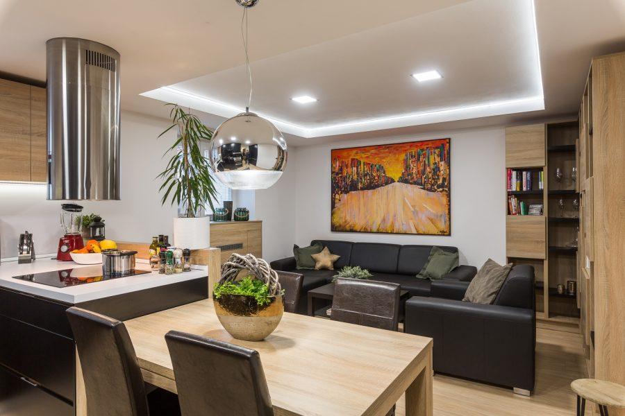 obývačka s čiernou sedacou súpravou a obrazom