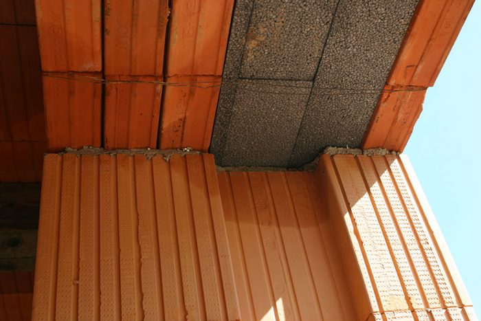 Na vrchnú stranu muriva ostenia otvoru sa nanesie vrstva murovacej tepelnoizolačnej malty min. v hrúbke 6 mm, do ktorej sa osadí jeden preklad z exteriérovej strany a tri preklady z interiéru. Do voľného priestoru medzi preklady sa vloží tepelná izolácia. Preklady sa zabezpečia stiahnutím viazacím drôtom.