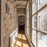 Chodba na poschodí je lemovaná oknami od podlahy po strop. Pôvodnému kameňu a tehle kontruje keramická dlažba v dekóre betónu.